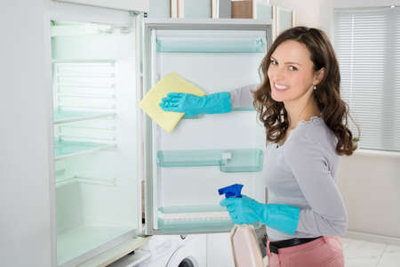 fridge: Young Woman Cleaning Refrigerator With Rag At Home Stock Photo