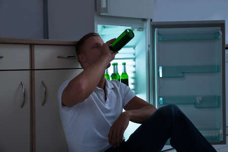 hombre tomando cerveza: Young Man Sitting Near The Cabinet And Drinking Beer In Kitchen Foto de archivo
