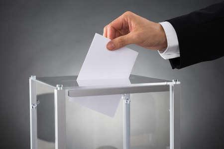 vorschlag: Close-up Der Wirtschaftler Hände setzen Stimmzettel in Box Am Schreibtisch