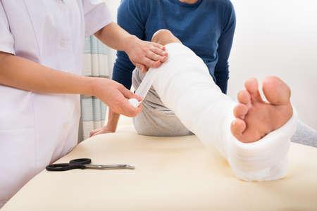 lesionado: Primer plano de la pierna de un paciente femenino Doctor en vendar Foto de archivo