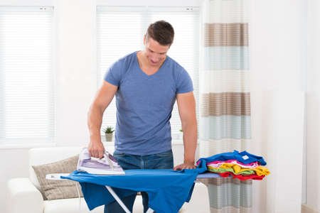 Hot house: Young Happy Man Ironing Clothes On Ironing Board