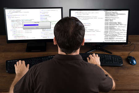 Young Man Programming Code On Computers Screen At Desk