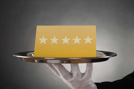 servings: Close-up Of Waiter Serving Plate With Star Rating