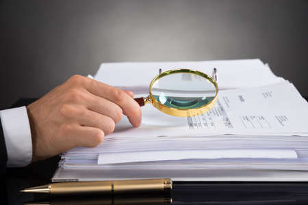 Close-up Of Businessperson Hands Analyzing Receipt With Magnifying Glass At Desk