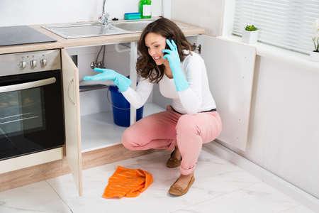 キッチンで携帯電話で話す若い女性