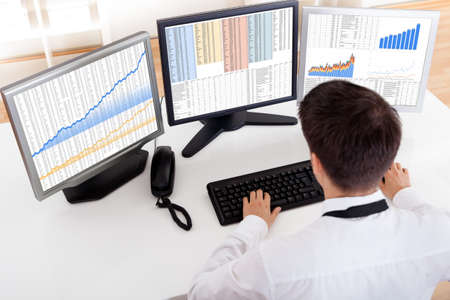 over the shoulder view: Over the shoulder view of the computer screens of a stock broker trading in a bull market showing ascending graphs Stock Photo