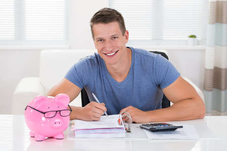 pensions: Happy Man With Piggybank Calculating Receipt At Desk Stock Photo