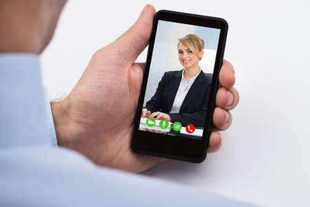 携帯電話で女性の同僚と実業家 Videochatting のクローズ アップ