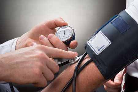 medical treatment: Close-up Of A Doctors Hand Checking Blood Pressure Of A Patient Stock Photo