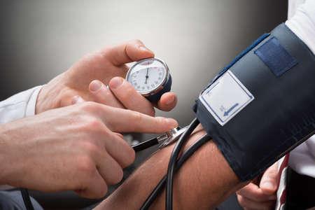 consulta médica: Primer De La Mano Comprobación de la presión arterial de un médico de un paciente