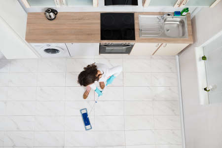 angle: High Angle View Of Woman Mopping Floor In Kitchen Stock Photo