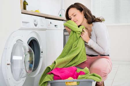 Mujer joven que se agacha con ropa limpios cerca de la lavadora electrónica