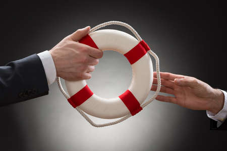 lifebuoy: Close-up Of Two Businessmans Hand Passing Lifebuoy Stock Photo