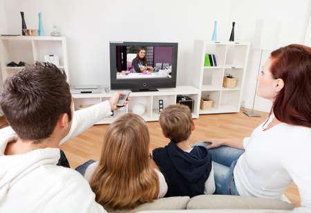 personas viendo television: Joven de la familia viendo la televisión juntos en casa Foto de archivo