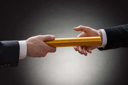 Close-up Of Two Businessmans Hand Passing A Golden Relay Baton