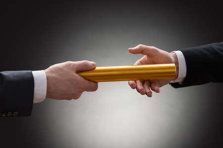 Close-up z ruky dvou podnikatel projde zlatou štafetu Reklamní fotografie