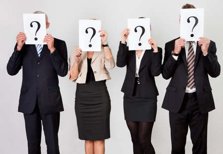 Group of unidentifiable business people hiding under question marks Фото со стока