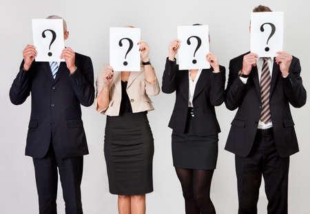 punto interrogativo: Gruppo di uomini d'affari non identificabile che si nasconde sotto i punti interrogativi Archivio Fotografico