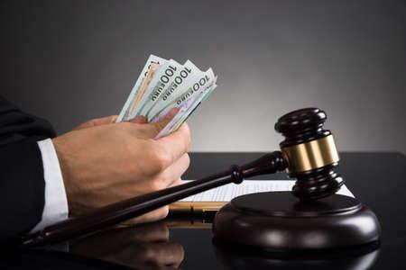 dinero euros: Primer plano de la jueza manos contando de billetes delante de Mazo En El Escritorio
