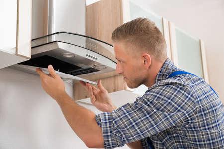 filters: Young Repairman Repairing Kitchen Extractor Filter In Kitchen Room