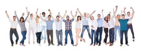 Happy Group Of People Dressed In Casual Raising Arm Over White Background