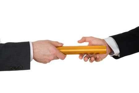 白い背景上黄金リレーのバトンを渡す 2 つのビジネスマンの手のクローズ アップ