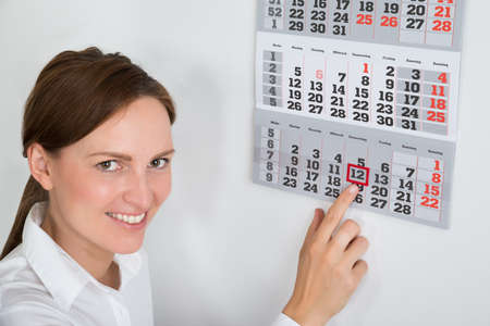 marking up: Close-up Of Young Businesswoman Placing Red Mark On Calendar Date