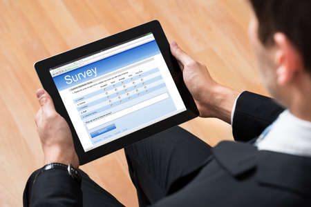online survey: Close-up Of Businessman Looking At Blank Online Survey Form On Digital Tablet