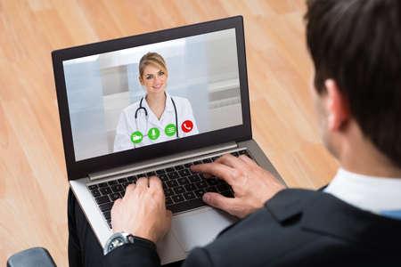 usando computadora: Primer De Empresario Videochatting línea con Doctor computadora portátil en el lugar de trabajo