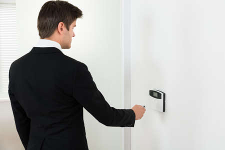 disarm: Young Businessman Using Remote Control For Operating Door Security System Stock Photo