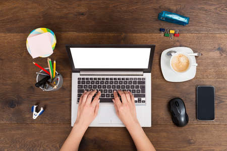 Close-up Of Person Hands Working On Laptop At Desk