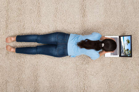 Young Woman Lying On Carpet While Looking At Photo On Laptop