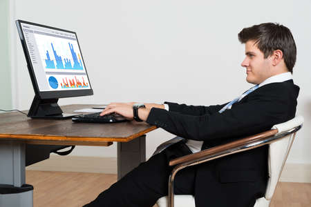 Young Businessman Leaning Back In His Chair While Analyzing Graph On Computer