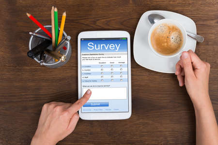 Close-up Of Person Hands Filling Survey Form On Mobile Phone At Desk Banque d'images