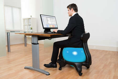 pilates man: Young Businessman Sitting On Blue Pilates Ball While Working On Computer In Office