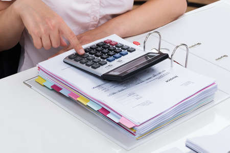 calculating: Close-up Of Businessperson Calculating Tax With Calculator At Desk