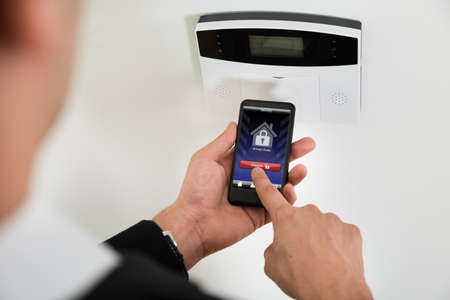 home security system: Close-up Of Businessperson Hands Disarming Security System Of Door With Mobile Phone