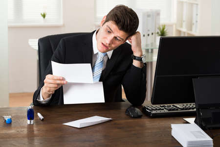 Portrait Of Young Shocked Businessman Looking At Document In Office Stock Photo