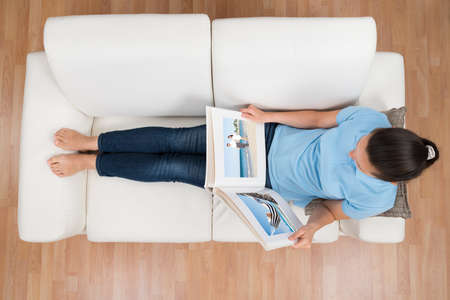 memories: High Angle View Of Young Woman Looking At Photo Album On Sofa Stock Photo