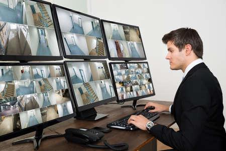 seguridad en el trabajo: Joven Operador Hombre Mirando a la c�mara de video m�ltiple en Inform�tica