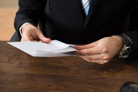 職場の机に封筒を持ったビジネスマンのクローズ アップ