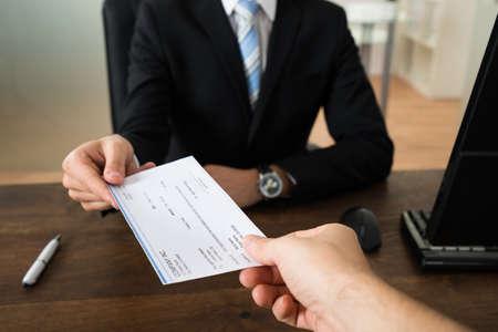schreiben: Close-up der Geschäftsmann Hände, welche Scheck zum anderen Person im Büro Lizenzfreie Bilder