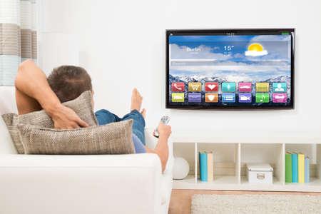 Mladý muž ležel na pohovce pomocí dálkového ovládání před televizními Reklamní fotografie