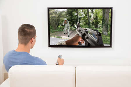 gun room: Young Man On Sofa Playing Game On Television