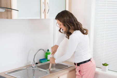 stoppage: Happy Woman Using Plunger In Kitchen Sink At Home Stock Photo