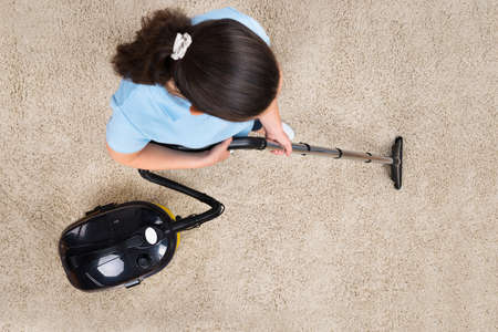 High Angle View Of Woman Cleaning Carpet With Vacuum Cleaner