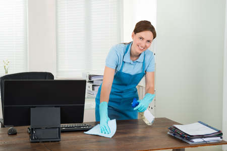 Office uniforms: Joven tur�stica feliz Trabajador de limpieza con trapo En Office