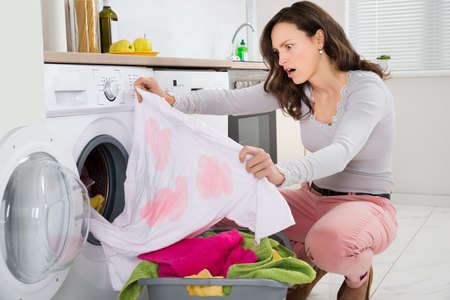 Shock Young Woman Looking At Stained Cloth In Kitchen
