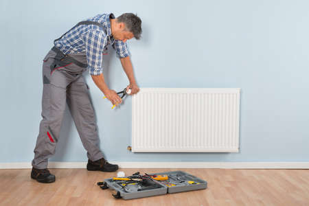 heat home: Portrait Of Mid-adult Male Plumber Repairing Radiator With Wrench Stock Photo