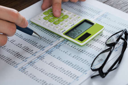 Close-up Of Person Hands Analyzing Accounting Document With Calculator
